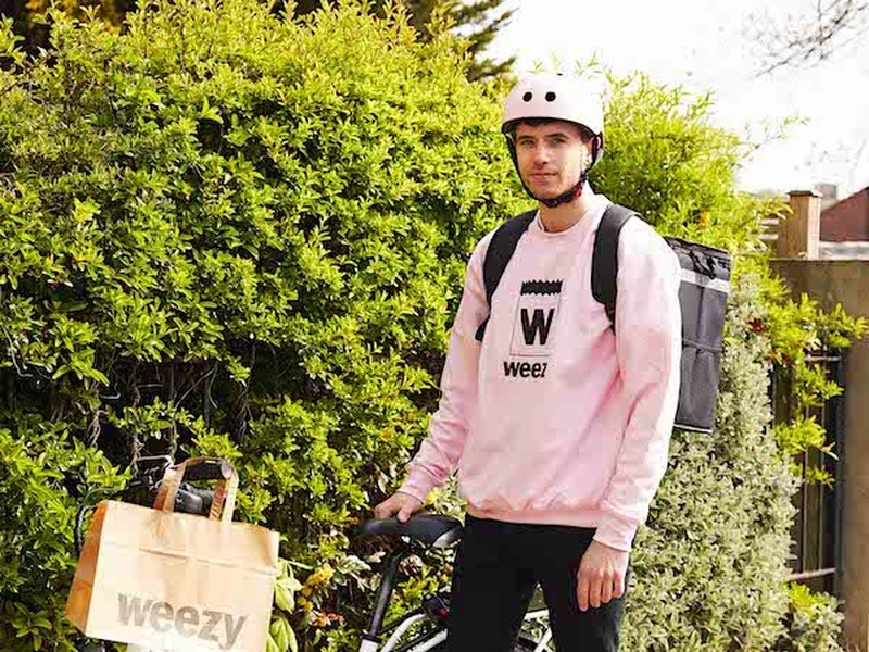 A Weezy Grocery Delivery Man In Pink Sweater And Crash Helmet
